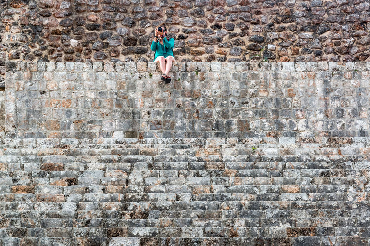 Full length of woman photographing while sitting on brick wall