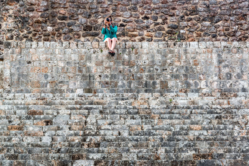 Tourist taking pictures from atop a pyramid in the Mayan ruins of Uxmal in Mexico Ancient Archaeology Architecture City Mayan Mayan Ruins Mexico Pyramid Riviera Maya Ruins Uxmal Uxmal Mexico Yúcatan America Building Civilization Culture Destination Maya Mexican Monument Riviera Stone Temple Tourism