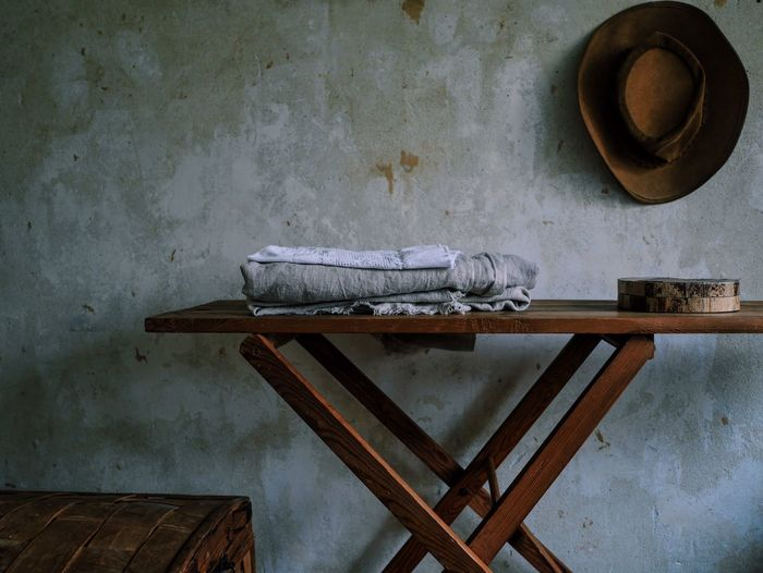 Fabrics On Table Against Hat On Wall At Home
