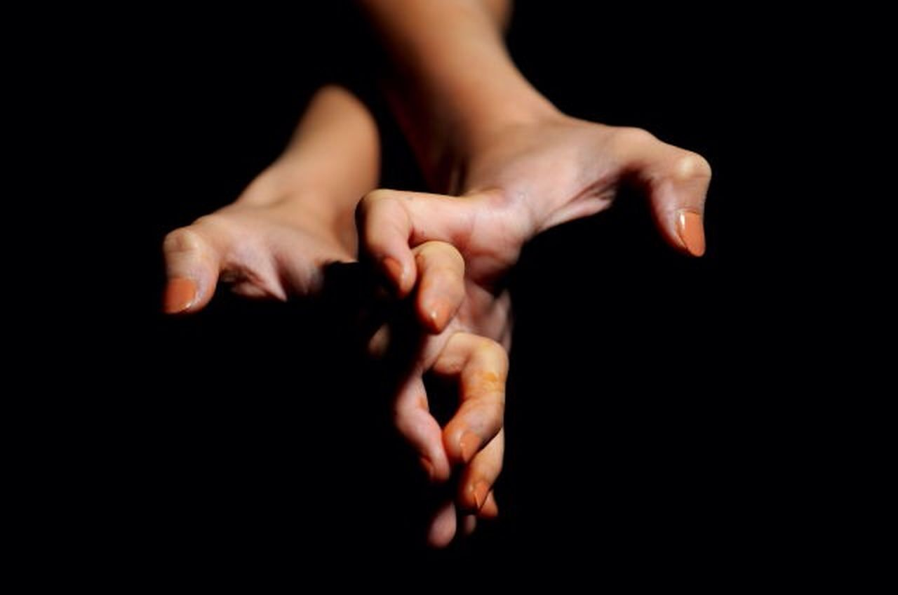CROPPED IMAGE OF HAND HOLDING OVER BLACK BACKGROUND