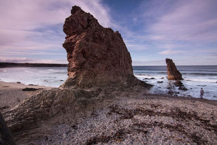 Headlands in calm sea against the sky