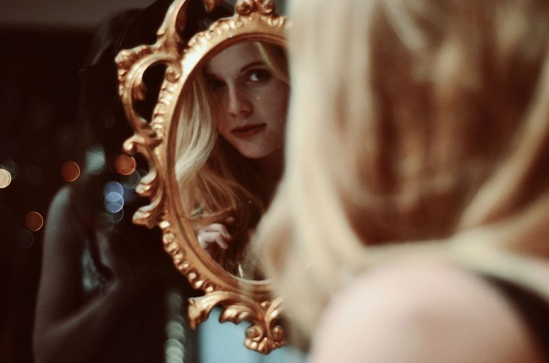 Close-Up Of Woman Looking At Reflection In Mirror