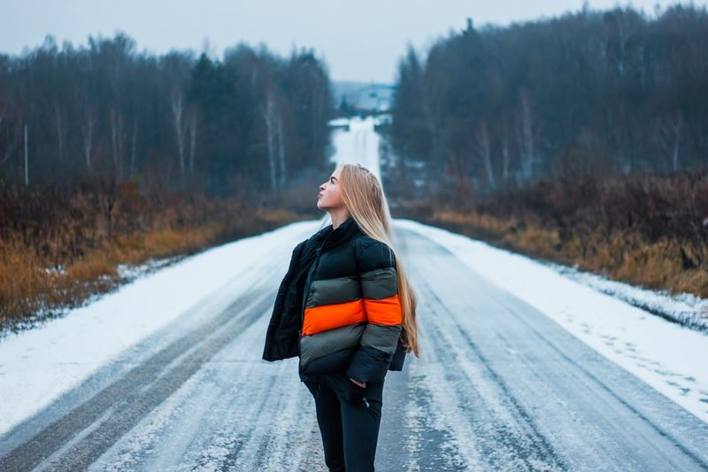 Woman standing on snow covered road during winter