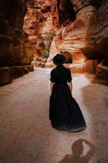 Rear view of woman standing against rock formation