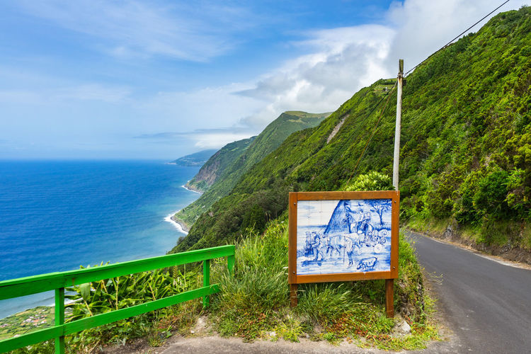 Seascape of Sao Jorge Island, Azores, Portugal Azores Portugal Beauty In Nature Cloud - Sky Communication Day Direction Horizon Horizon Over Water Mountain Nature No People Outdoors Plant Road Sao Jorge Island Scenics - Nature Sea Sign Sky Tranquil Scene Tranquility Water