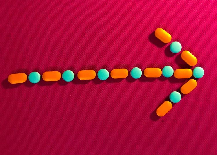 Directly above shot of arrow symbol made from medicines on red textile
