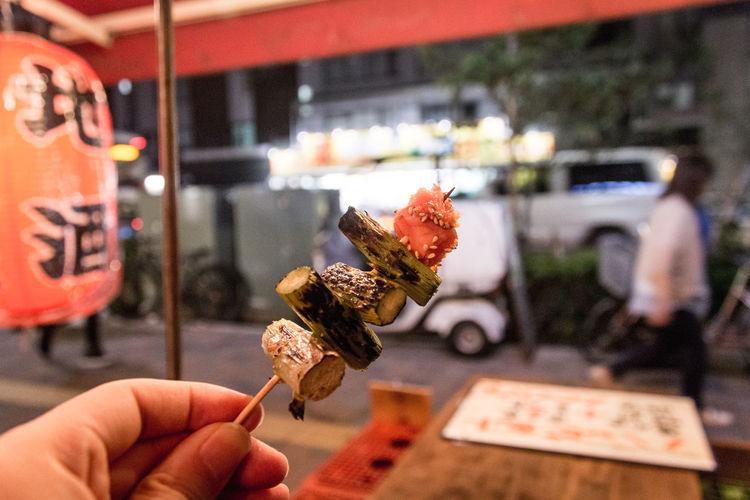 Cropped Image Of Hand Holding Kushiyaki On Street