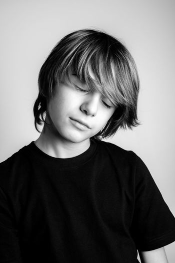 Cute Boy With Eyes Closed Against White Background