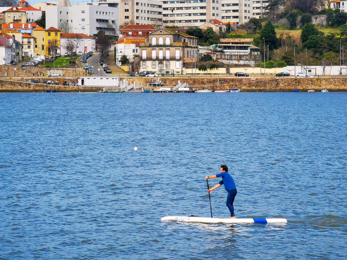 Full length of man with umbrella on sea in city
