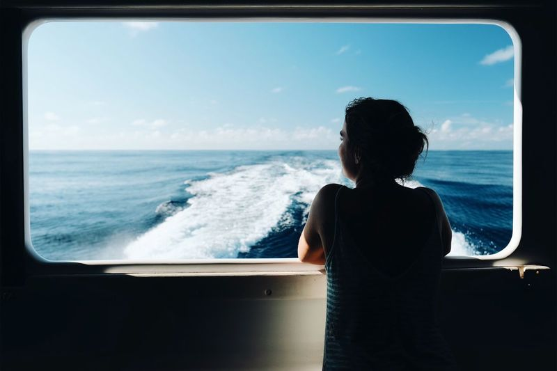 Window of freedom Sea Rear View Horizon Over Water Looking At View One Person Sitting Sky Wave Day Nature Real People Water Scenics Beach Beauty In Nature Indoors  Adult People