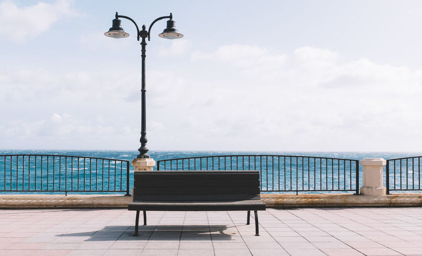 Empty Bench At Promenade Against Sky