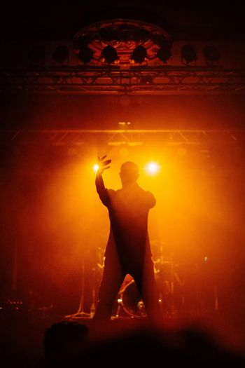 Silhouette man with arms raised standing at music concert