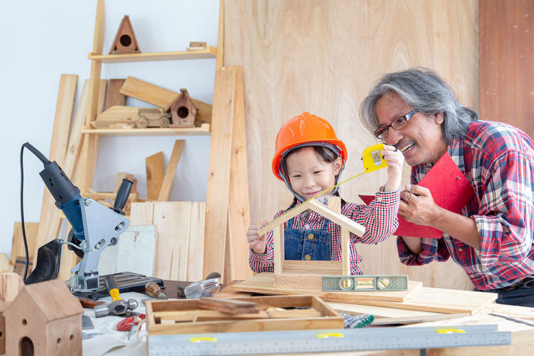 Girl with grandfather making model house at workshop