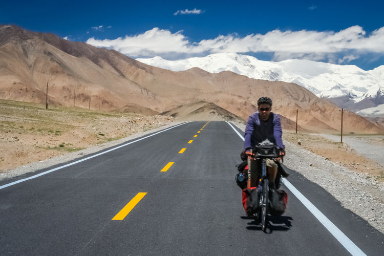 Man riding bicycle on road against mountain range