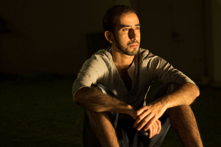 Man Looking Away While Sitting On Field At Night
