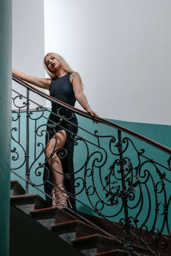 Low angle view of beautiful woman wearing dress while standing on staircase