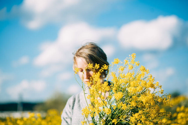Close-up of woman by yellow flower on field against sky