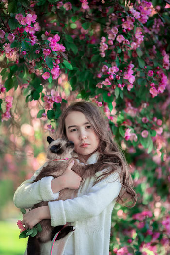 Portrait of girl with cat standing against flowering plant