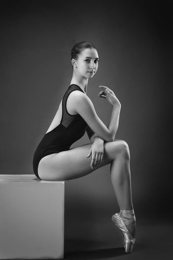 Side view portrait of ballet dancer sitting on box against gray background