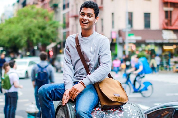 Portrait of smiling young man on street in city