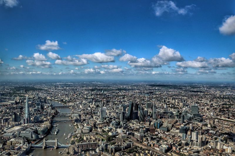 Aerial view of cityscape with thames river against sky