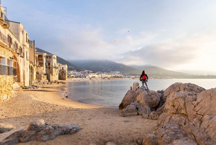 Man on rock at beach against sky