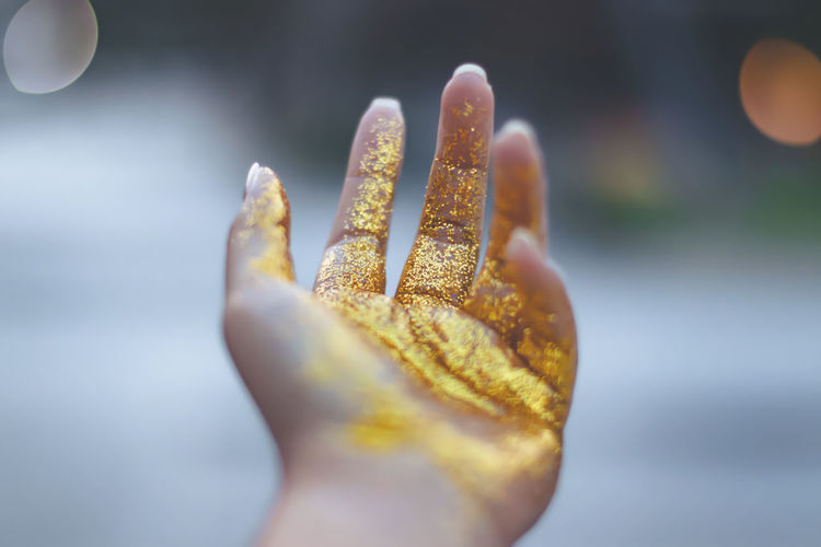 Cropped hand of woman with golden glitter