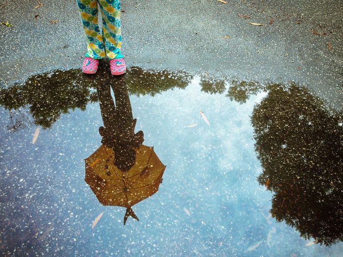 Girl Standing With Umbrella Reflecting On Puddle During Rainy Season