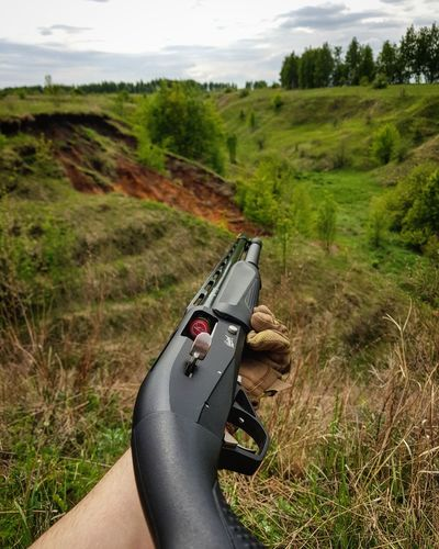 Grass Day Adventure Human Body Part Grass Area Nature Weapon Outdoors Landscape Human Hand Adult Close-up One Person Adults Only Sky People gun Beatiful Jorney First Eyeem Photo