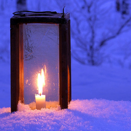 Close-up of lit candle on snow covered land