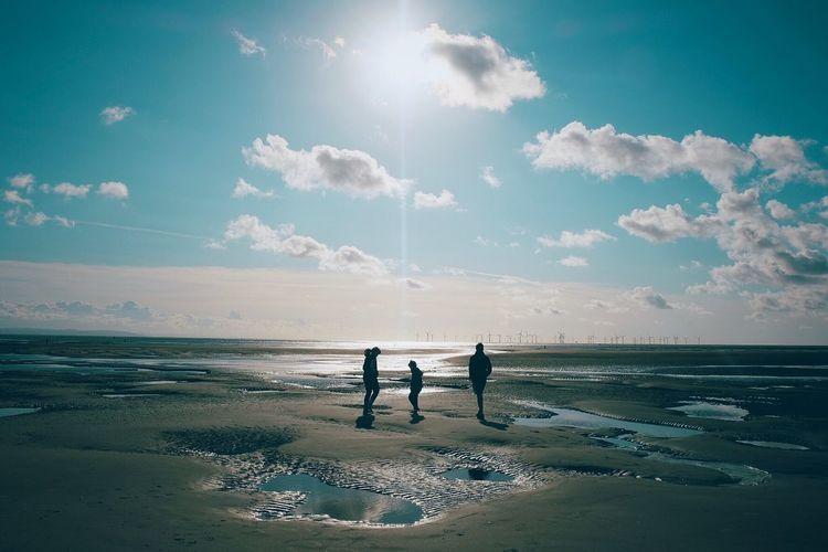 People on beach against sky