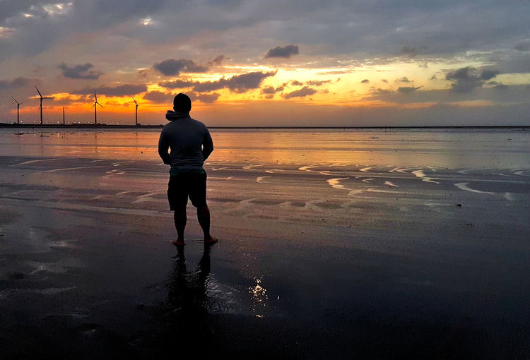 Rear view of man on beach against sky during sunset