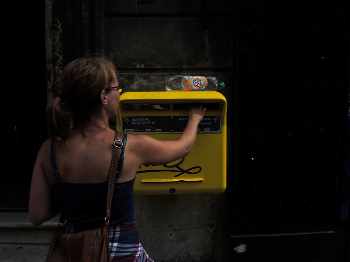 Rear view of woman putting envelope in mailbox