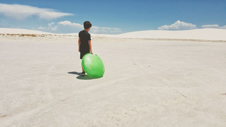 Rear View Of Boy Holding Plastic Sled While Walking At White Sands National Monument