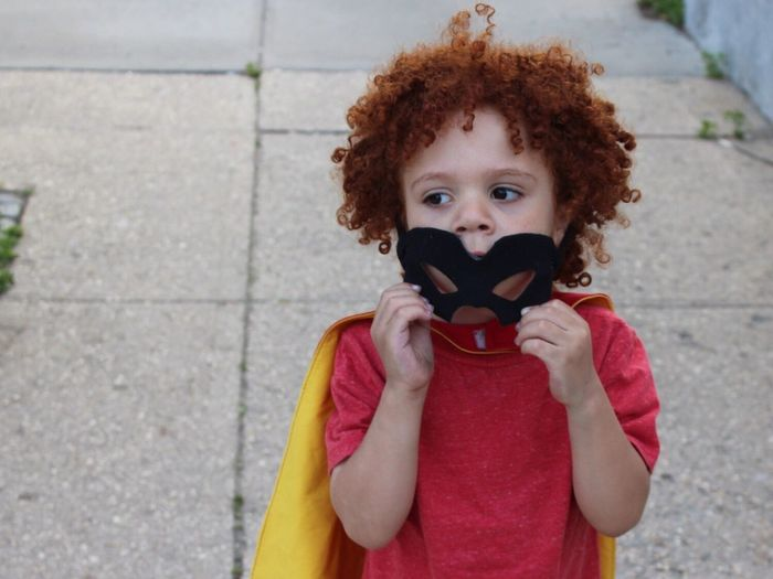 Boy with curly redhead wearing costume standing on footpath