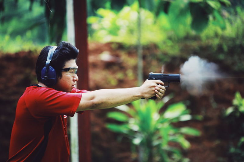 Side View Of Young Man Aiming Handgun While Standing Against Plants