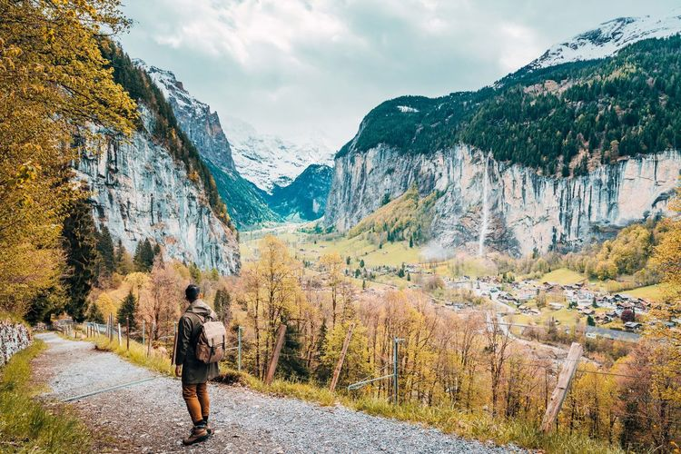 Man walking on footpath against mountains