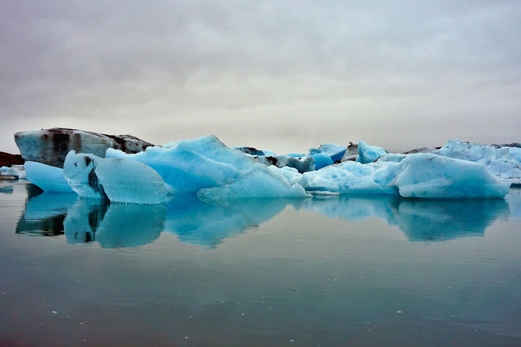 Icebergs In Lake Against Cloudy Sky
