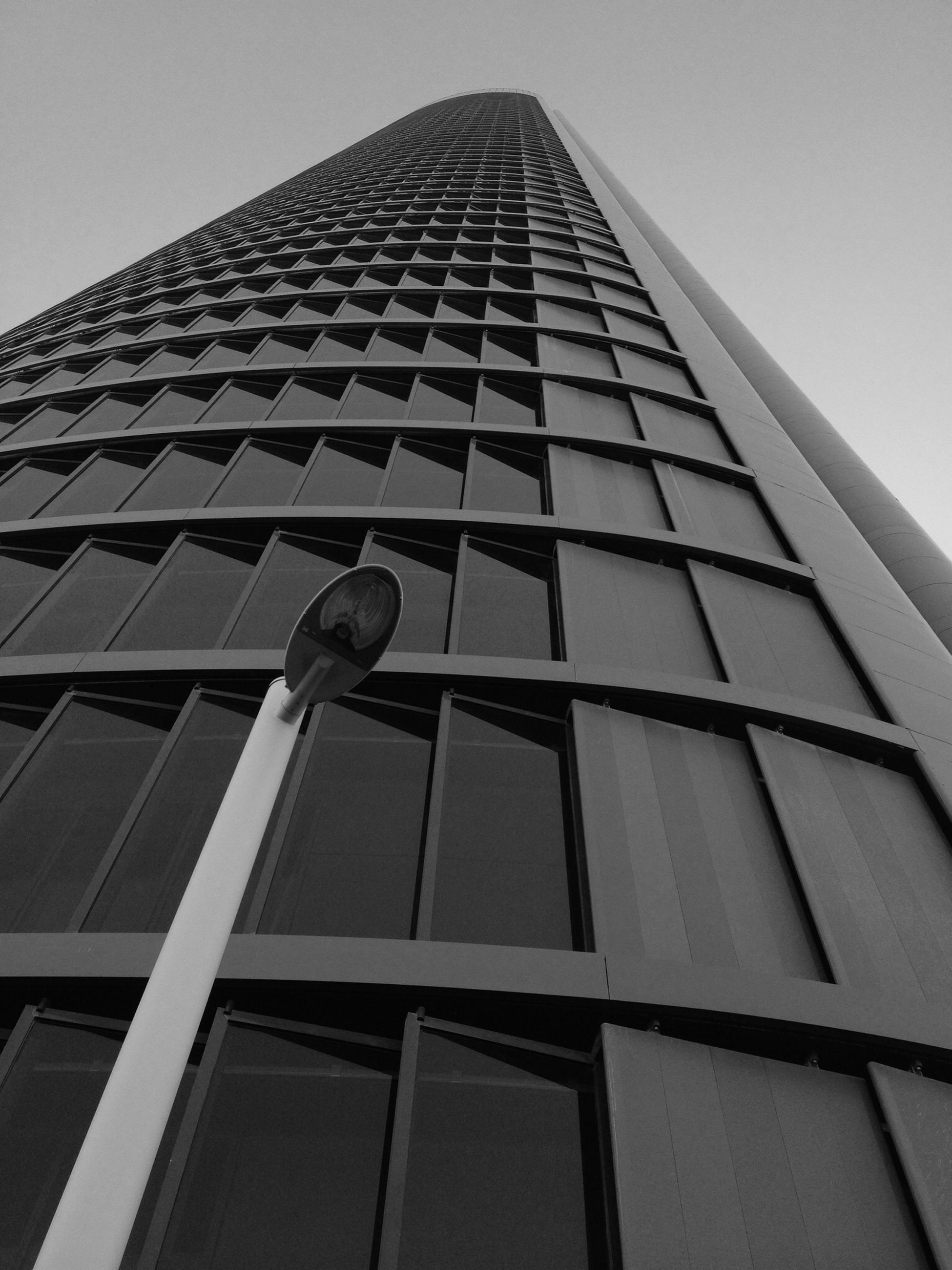 low angle view, architecture, building exterior, built structure, tall - high, tower, modern, office building, skyscraper, city, building, sky, clear sky, glass - material, window, tall, day, outdoors, no people, reflection