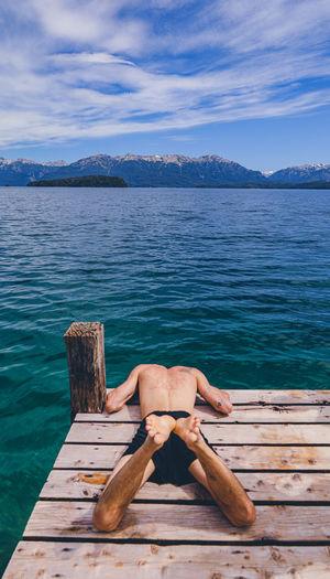 Man lying on wood by sea against sky