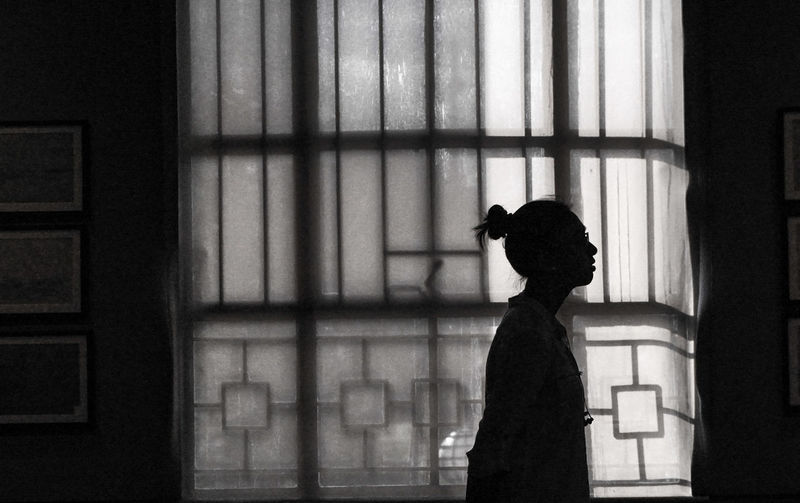 Side view of silhouette woman standing against window