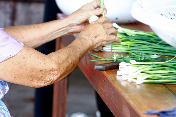 Midsection of senior woman cleaning spring onions at home