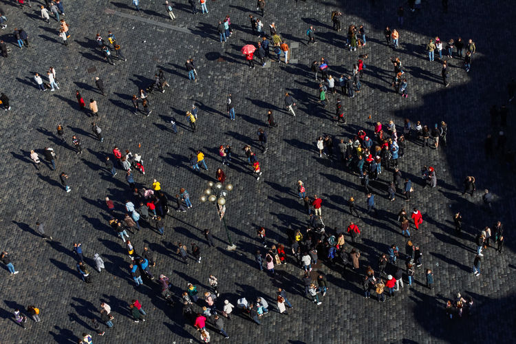 High angle view of people and long shadows on street