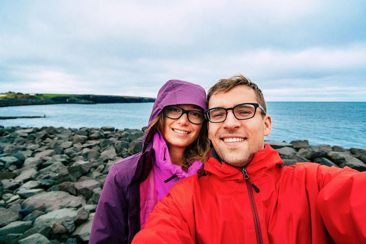 Happy best friends, man and woman in warm clothes making selfie on Gullfoss Waterfall background, Iceland. Couple visiting famous tourist attractions and landmarks in Icelandic nature landscape. Iceland Adult Adults Only Day Eyeglasses  Friendship Happiness Horizon Over Water Looking At Camera Nature Outdoors People Portrait Real People Sea Selfie Sky Smiling Standing Togetherness Travel Destinations Two People Water Young Adult Young Women