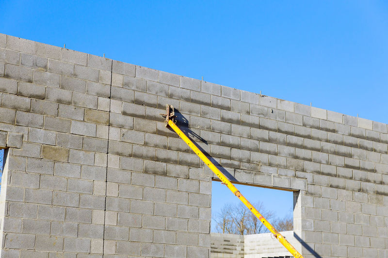 Low angle view of metallic pile by wall against sky outdoors