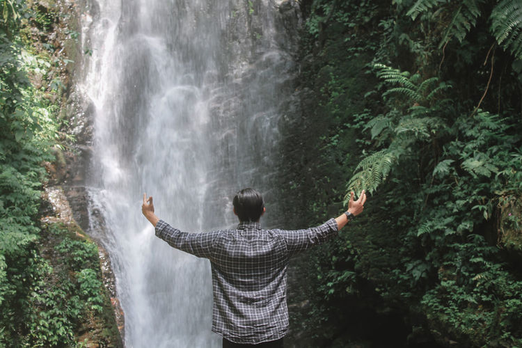 Rear view of man with arms outstretched looking at waterfall in forest
