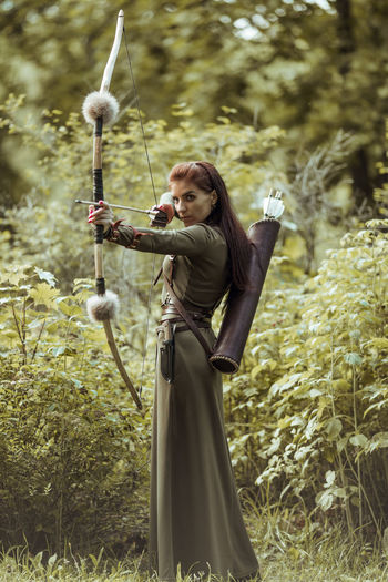 Beautiful archer holding bow and arrow standing against trees