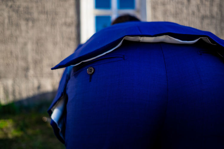 Rear view of man against blue wall