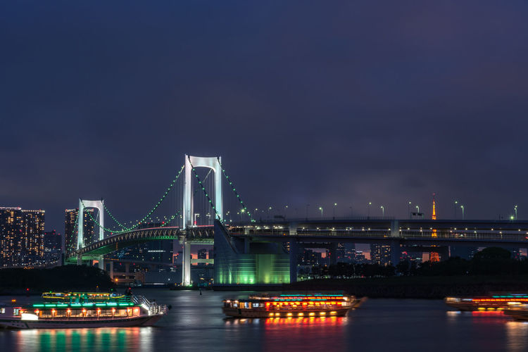 View of bridge over river in city at night