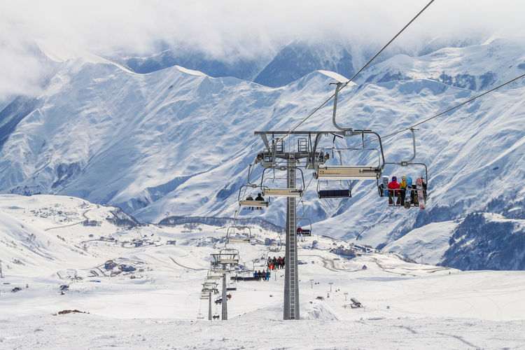 Chairlift with people at the ski resort. against the background of snow-capped peaks